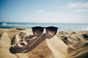a pair of sunglasses laying in the sand