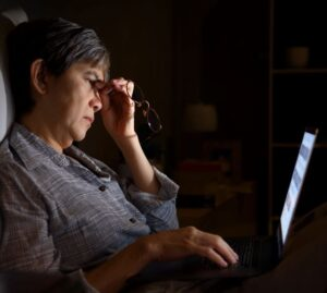 a woman having difficulty looking at her computer screen
